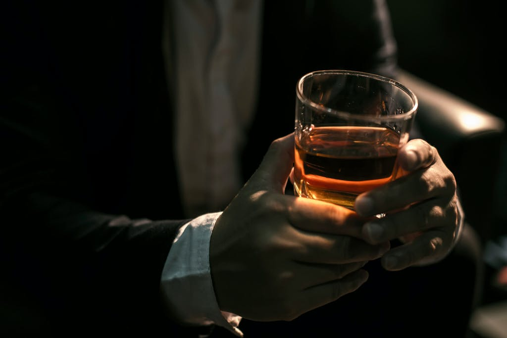 Man holding a glass of whiskey