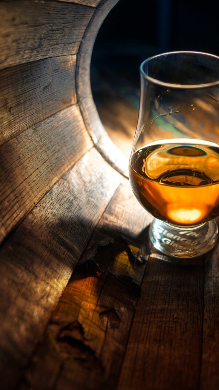 Glass of whiskey inside a wood barrel